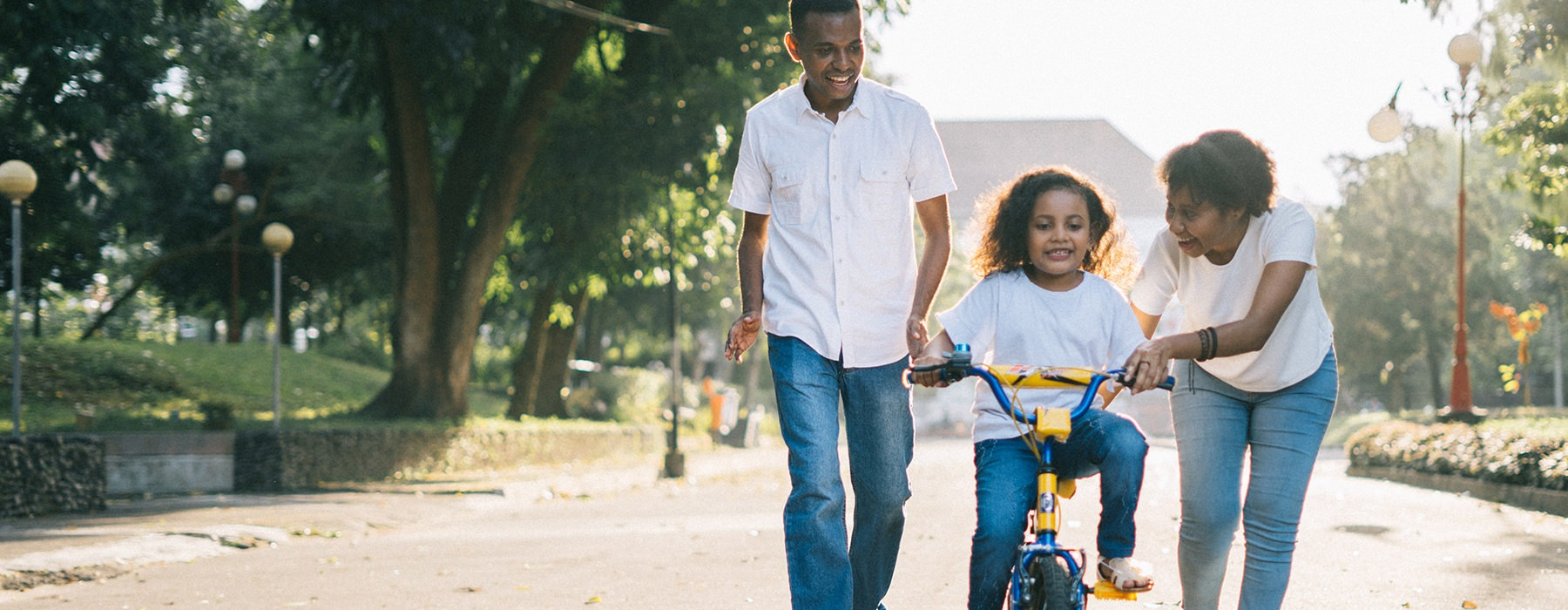 mother and father teaching daughter to ride a bike